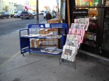 Stands with newspapers for sale outside a store. Newspaper stand outside a local store in Queens New York royalty free stock photo