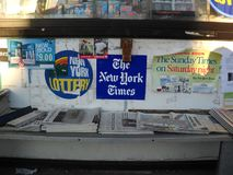 Stands with newspapers for sale outside a store. Newspaper stand outside a local store in Queens New York stock images