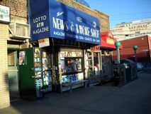 Stands with newspapers for sale outside a store. Newspaper stand outside a local store in Queens New York royalty free stock images