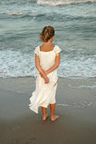 She stands on the shore. Little girl stands out on the sand of the ocean as teh sun sets behind her and watches the crashing waves Stock Photo