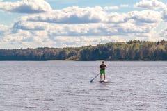 Standup Paddeleinstieg des Mannes Bild des jungen Mannes SUP surfend auf den See stockfotografie
