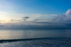 Standup paddle on blue ocean water, single person iconic view stock photo