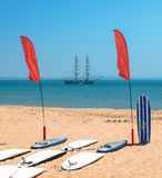 Standup Paddle boards on beach with bokeh caravel in background.  stock photo