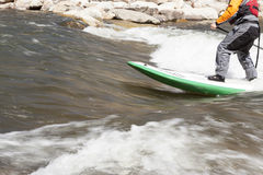 Standup Paddleboard on a swift river. A man in a swift rapid rides a green and white standup paddleboard Royalty Free Stock Images