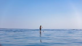 Standup paddleboarding, supsurfing mężczyzna w Adriatyckim morzu w Chorwacja zdjęcia stock