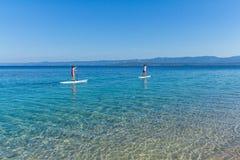 Standup skovelboarders på Zlatni tjaller stranden, Kroatien royaltyfria foton