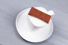 Stange der Milchschokolade auf einer weißen Schale Milch Lizenzfreie Stockfotos