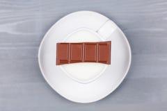 Stange der Milchschokolade auf einer weißen Schale Milch Lizenzfreie Stockbilder