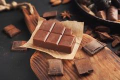 Stange der Milchschokolade auf hölzernem Schneidebrett Stockfoto