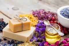 Stangen von selbst gemachten Seifen, Honig oder Öl und Haufen von heilenden Kräutern Lizenzfreies Stockfoto