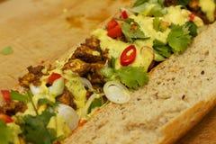 Stangenbrot mit gebratenem Huhn und Currysoße Stockbilder