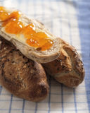 Stangenbrot mit Samen bei Tisch mit Butter Lizenzfreies Stockbild