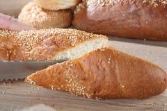 Stangenbrotausschnitt auf dem Hintergrund von Brötchen und von Brot stockfotos