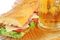 Stangenbrotsandwichnahaufnahme mit Bier lizenzfreie stockfotografie