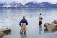 staning在海洋和钓鱼在Seward的两个人 免版税库存图片