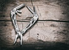 Stanless steel multitool on wooden background royalty free stock image