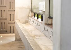 Stanless steel taps above concrete sink in shared toilet with yellow sunlight. royalty free stock photo