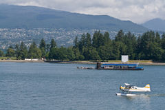 Stanley Park floatplane. Stanley Park and North Vancouver form the backdrop of a floatplane arrival in Vancouver, BC, Canada Royalty Free Stock Photography