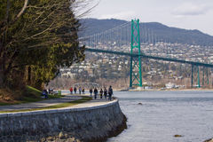 Stanley Park skyddsmur mot havet med den iconic lejonportbron arkivbilder