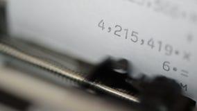 Stansa nummer in i en printingräknemaskin arkivfilmer