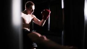 Stansmaskiner för ung man i boxningidrottshall arkivfilmer