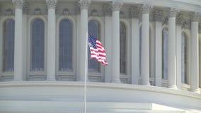 Stany Zjednoczone kapitał - zakończenie flaga amerykańskiej latanie w wiatrze na Kapitałowym budynku zbiory