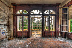 Stanza abbandonata con la vista attraverso il bello conservatorio rotto Fotografia Stock