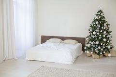 Stanza bianca della decorazione con i regali di Natale del nuovo anno del letto Fotografia Stock