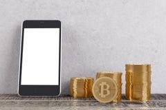 Stanza con i bitcoins e lo smartphone Fotografie Stock