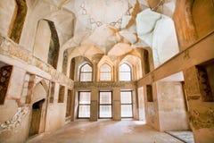 Stanza con il camino ed affreschi sbiaditi sulle pareti del palazzo storico in Medio Oriente Immagine Stock