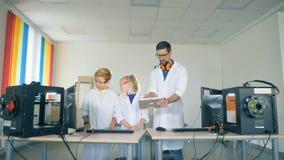 Stanza dei giochi del laboratorio con un socio maschio che dimostra un esperimento agli anni dell'adolescenza video d archivio
