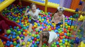 Stanza dei giochi del ` s dei bambini I bambini giocano in un bacino asciutto riempito di palle colorate di plastica stock footage