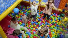Stanza dei giochi del ` s dei bambini I bambini giocano in un bacino asciutto riempito di palle colorate di plastica archivi video