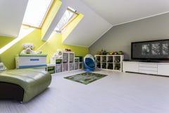 Stanza di bambino alla soffitta con il set televisivo fotografia stock