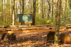 Stanza di classe all'aperto in foresta con il bordo di gesso ed i banchi di legno fotografia stock