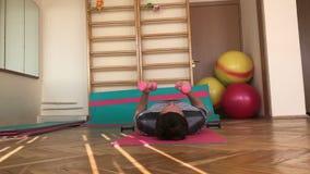 Stanza di ginnastica Giovane che fa un insieme degli esercizi con le teste di legno video d archivio