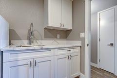 Stanza di lavanderia con i gabinetti superiori di marmo del parete di taupe e immagine stock