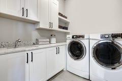 Stanza di lavanderia moderna pulita bianca con la rondella e l'essiccatore fotografie stock