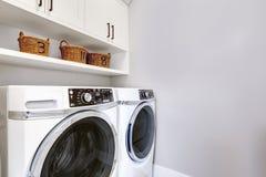 Stanza di lavanderia pulita bianca moderna con la rondella e l'essiccatore fotografia stock