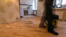 Stanza di pulizia del lavoratore del carpentiere dopo l'installazione del bordo di legno del parquet durante il timelapse del lav stock footage