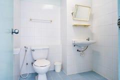 Stanza generica della sciacquone dell'appartamento o piccolo hotel con la toilette con sciacquone, il lavandino e lo specchio di  Fotografia Stock Libera da Diritti