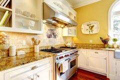 Stanza gialla luminosa della cucina con le cime del granito Fotografia Stock