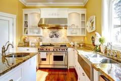 Stanza gialla luminosa della cucina con le cime del granito Immagine Stock