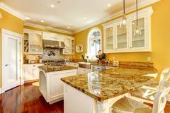 Stanza gialla luminosa della cucina con le cime del granito Fotografia Stock Libera da Diritti