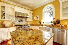 Stanza gialla luminosa della cucina con le cime del granito Fotografie Stock Libere da Diritti