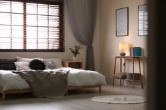Stanza moderna interna con i ciechi di finestra e del letto matrimoniale fotografie stock