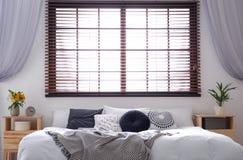 Stanza moderna interna con i ciechi di finestra e del letto matrimoniale immagine stock