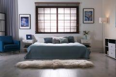 Stanza moderna interna con i ciechi di finestra e del letto matrimoniale fotografia stock libera da diritti