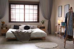 Stanza moderna interna con i ciechi di finestra e del letto matrimoniale fotografia stock