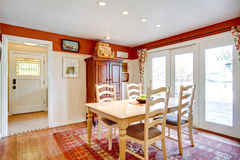 Stanza semplice della cucina di colori caldi con una piccola area pranzante Fotografia Stock Libera da Diritti